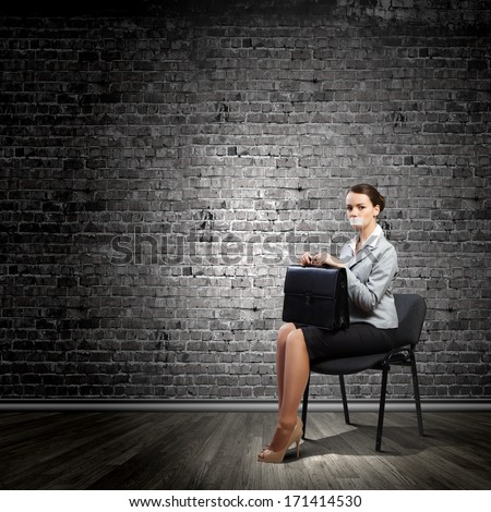 Young speechless businesswoman with adhesive tape on mouth - stock photo