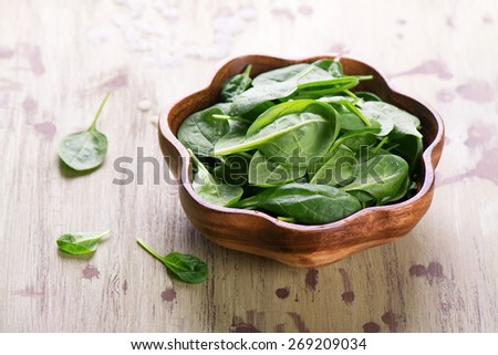 Young spinach leaves in a wooden bowl on wooden background. Selective focus - stock photo