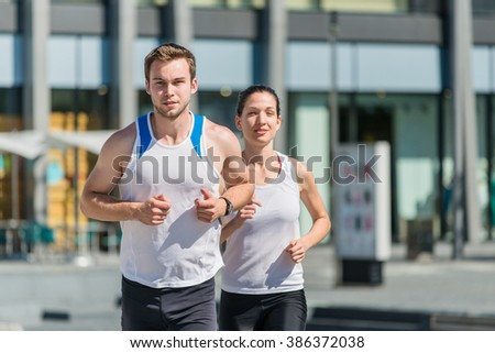 Young sport couple jogging in city environment - man first - stock photo