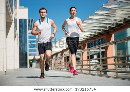 Young sport couple jogging together in city environment - stock photo
