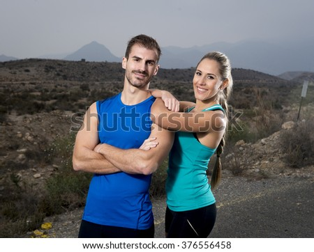 young sport couple posing shoulder to shoulder looking cool and smiling happy  girl wearing cyan tank top and man blue singlet both with folded arms in fitness club advertising style