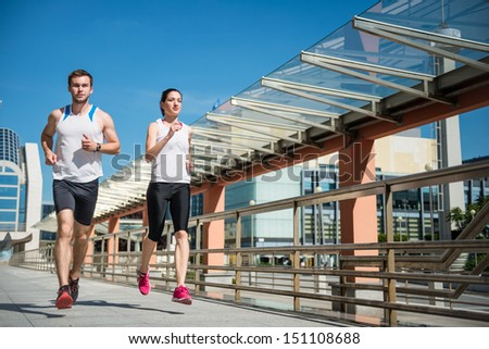 Young sport couple running together in city environment - stock photo