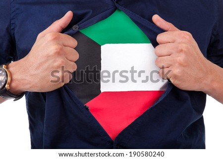 Young sport fan opening his shirt and showing the flag his country Kuwait, kuwaiti flag - stock photo