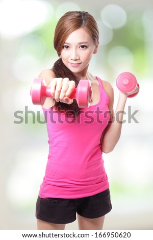 Young sport girl with dumbbells with green background, asian - stock photo
