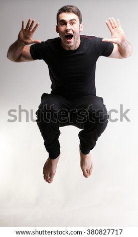 Young sport man jumping over grey background