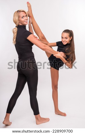 Young sport  mother and her   daughter teenager doing splits  looking at camera  isolated on white background with copy place