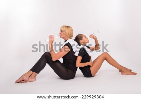 Young sport  mother and her  daughter teenager sitting on floor drinking clear mineral water isolated on white background with copy place - stock photo