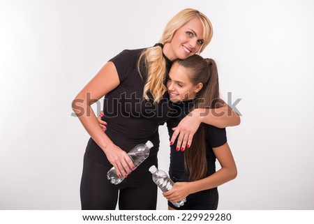 Young sport  mother embracing  and hugging  her  daughter teenager with bottle  clear mineral water  and towel isolated on white background - stock photo