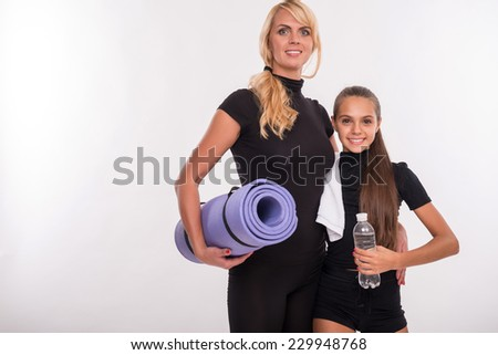 Young sport  mother with rubber mat for yoga  and her  daughter teenager with bottle  clear mineral water  and towel isolated on white background with copy place - stock photo