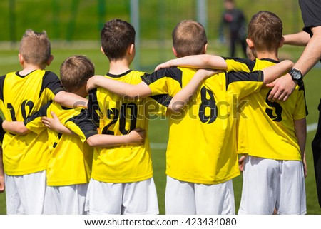 Young sport team with coach on sports field. Football; soccer; handball; volleyball; match for children. Youth sports team standing together. football soccer game. team work and penalty kick - stock photo