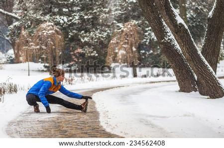 Young sport woman doing exercises during winter training outside in cold snow weather in park - stock photo