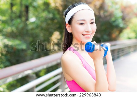 young sport woman exercising with blue dumbbell in the park. - stock photo