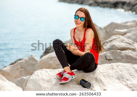 Young sport woman in red shirt and sneakers having rest with mobile phone on the rocky beach in the morning