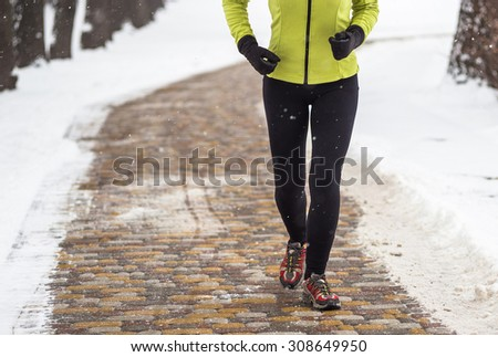 Young sport woman jogging during winter training outside in cold snow weather - stock photo