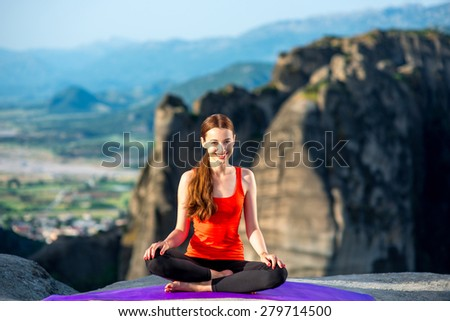 Young sport woman meditating on the mat in the mountains - stock photo