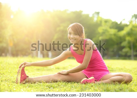 Young sport woman stretching and preparing to run in park. asian - stock photo