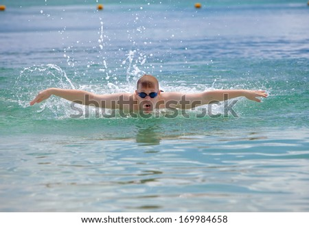 young sporting man swims in the sea butterfly stroke style.   - stock photo