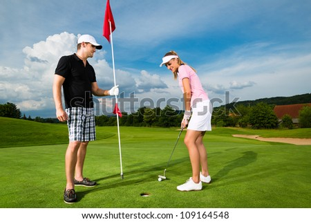 Young sportive couple playing golf on a golf course, she is putting at the green - stock photo