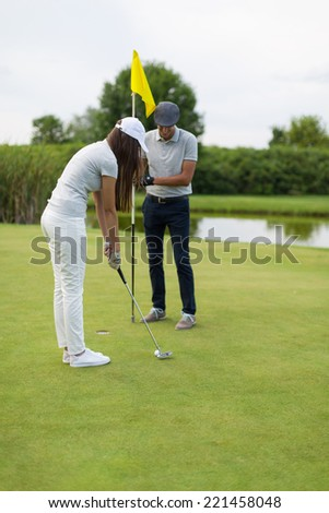 Young sportive couple playing golf on a golf course. Young trainer teaching female some basics - stock photo
