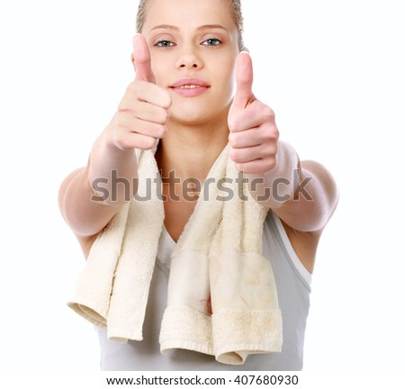Young sportive girl with towel showing ok, isolated on white background
