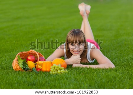 Young sportive woman lying on a grass with basket of fruits and vegetables - stock photo