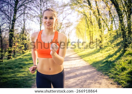 Young sportive woman training in a park for marathon - Athlete running outdoors at sunset - Attractive girl making sport to lose weight and stay fit - stock photo
