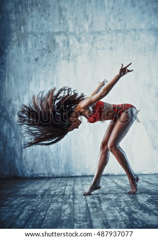 Young sports brunette woman shaking hair on old wall background