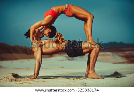 Young sports couple doing acroyoga exercises on sand beach and kissing