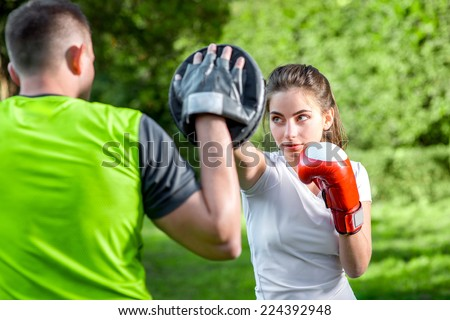 Young sports couple training to box in the park - stock photo