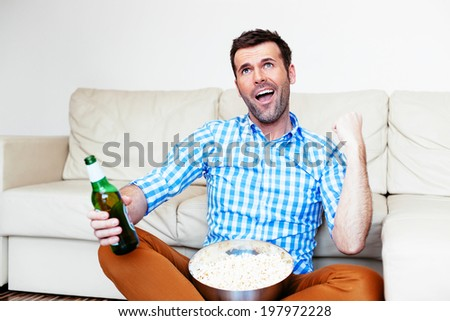 Young sports fan watching a game and celebrating his team victory - stock photo