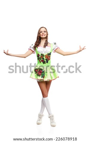 Young sports flexible girl in traditional Russian folk costume. Young female dancer standing in national costume on isolated white background. - stock photo