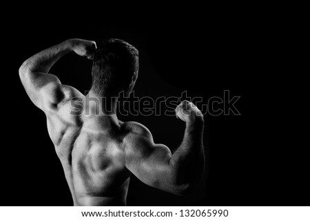 Young sports guy with a naked torso on a black background