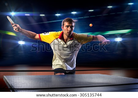 young sports man tennis player is playing on black background with lights - stock photo