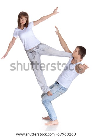 Young sports people carry out acrobatic tricks on a white background. Concept of teamwork. - stock photo