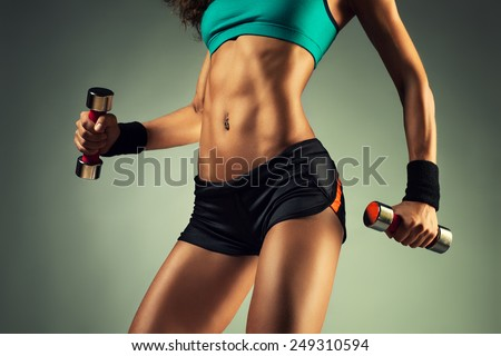 Young sports sexy fitness woman body with dumbbells posing on wall background. - stock photo