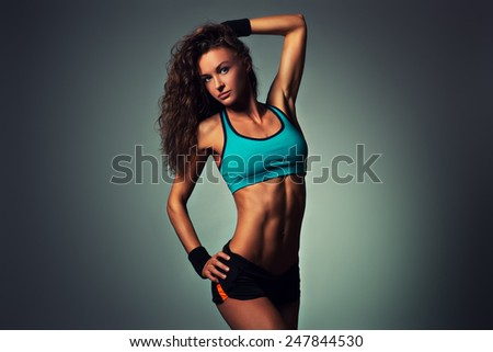 Young sports sexy fitness woman posing on wall background. - stock photo