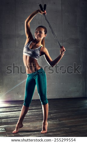 Young sports sexy fitness woman with skipping rope on wall background. - stock photo