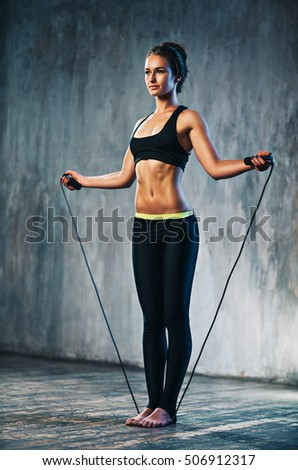 Young sports sexy fitness woman with skipping rope on wall background