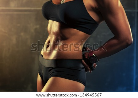 Young sports woman abdominal muscles.