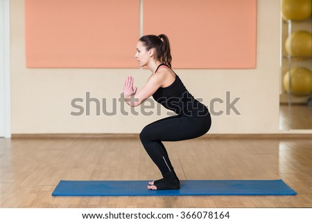 Young sports woman doing squats and holds hands namaste. Indoor gym. Utkatasana - Chair Pose. - stock photo