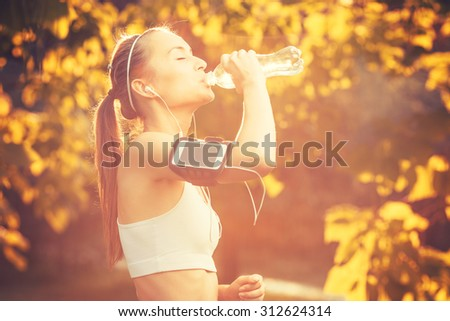 Young sports woman drinking fresh water from the bottle in the autumn sunny park refreshing herself.  Sport lifestyle. - stock photo