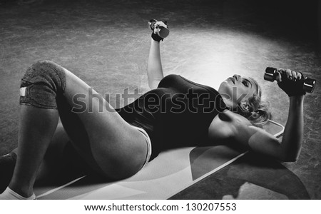 Young sports woman dumbbells exercises. Black and white.