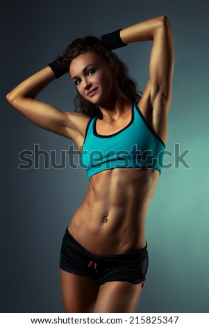 Young sports woman on wall background.