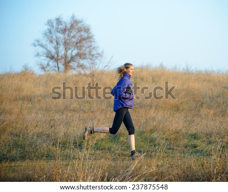 Young Sports Woman Running on the Trail in the Autumn Field. Active Lifestyle