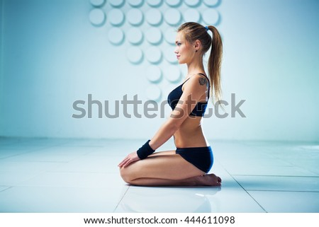 Young sports woman sitting and resting in modern white and blue interior. Tattoo on body. - stock photo