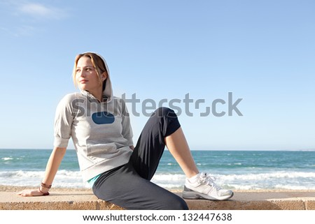 Young sports woman sitting by a beach, taking a break from exercising and being thoughtful against a blue sky. - stock photo