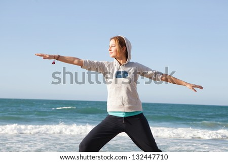 Young sports woman stretching her arms and legs while exercising on a beach during a sunny morning with a blue sky and the sea in the background. - stock photo
