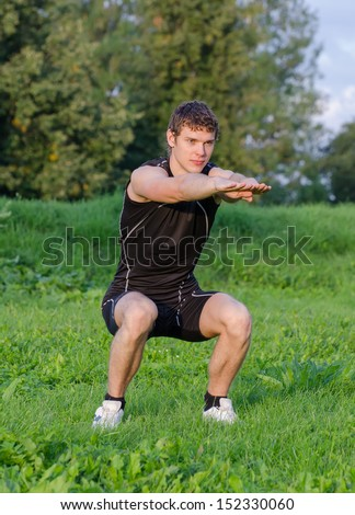 Young sportsman crouches before workout in park - stock photo