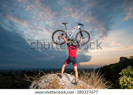 Young sportsman cyclist raising the mountain bike above his head with success on top of the hill.