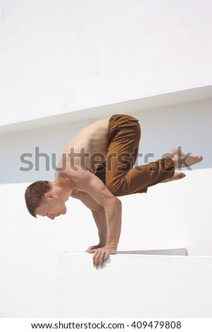 Young sportsman doing exercise near white wall with naked torso